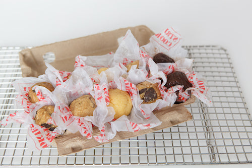 balls of cookie dough in an egg carton container on top of a baking rack