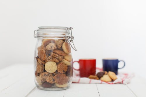 a jar filled with mini cookies and two espresso cups in the background