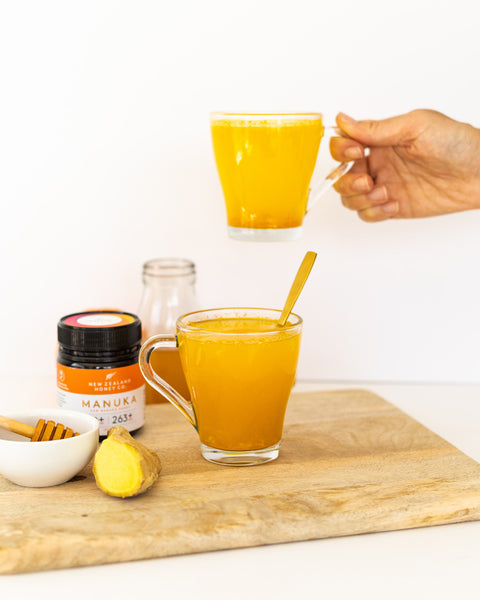 A hand holding a cup of the finished immunity drink with Manuka Honey