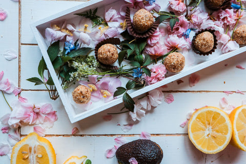 Manuka honey bliss balls on a platter with flowers
