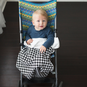 White baby boy sitting in stroller with houndstooth GoBlanket. Black and white houndstooth Bazzle Baby GoBlanket. Features clips on the sides of the blanket to ensure it stays put on the car seat, stroller or clothing. Cotton front and fleece back.