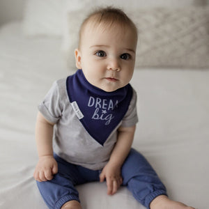 "Bazzle Baby bandana drool bib that's navy blue with lighter blue writing that says ""dream big."""