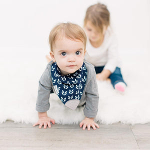 Bazzle Baby bandana bib with teether in nay with white floral designs and grey attached teether.