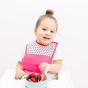 Bazzle Baby Foodie Silicone and Fabric Bib in pink and white triangles.