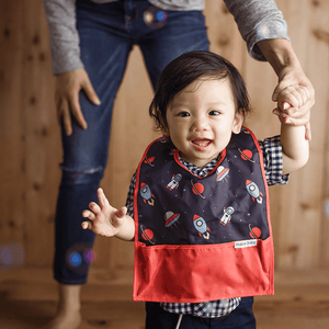 Asian American baby boy wearing the Space Cadet travel bib. The only travel bib that folds into itself. Bazzle Baby GoBibs clip to bags and strollers. Bottom pocket catches all the mess. Made of nylon to prevent stains and soak-through. Adjustable velcro allows the bib to grow with baby.