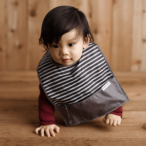 Boy wearing the black and white striped GoBib. It features a grey border and bottom catch-all pocket. The only travel bib that folds into itself. Bazzle Baby GoBibs clip to bags and strollers. Bottom pocket catches all the mess. Made of nylon to prevent stains and soak-through. Adjustable velcro allows the bib to grow with baby. Designed for baby boy and baby girl.