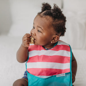 Baby girl eats while wearing the Bazzlebaby GoBib. This one is pink and white chunky stripes with teal border and bottom pocket.