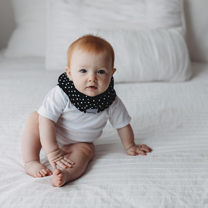White baby girl wearing the black scarf bib with white polka dots. The Bazzle Baby BandoBib is an infinity-style scarf drool bib that provides extra warmth and style. 100% cotton to soak up all the drool and mess. Nickel-free adjustable snaps in the back allow the bib to grow with baby