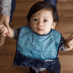 Asian American baby boy wearing the Blue Galaxy Bazzle Baby GoBib. The only travel bib that folds into itself. Bazzle Baby GoBibs clip to bags and strollers. Bottom pocket catches all the mess. Made of nylon to prevent stains and soak-through. Adjustable velcro allows the bib to grow with baby. Designed for baby boys.
