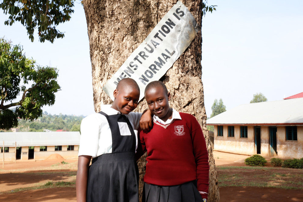 School pupils Irene and Winfred from Uganda, in front of a sign saying 'menstruation is normal'.