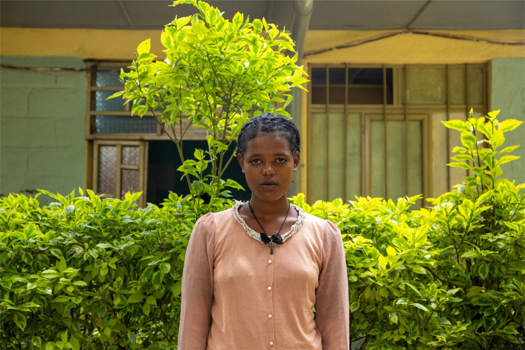 15-year-old Askale standing in front of her school in Addis Ababa