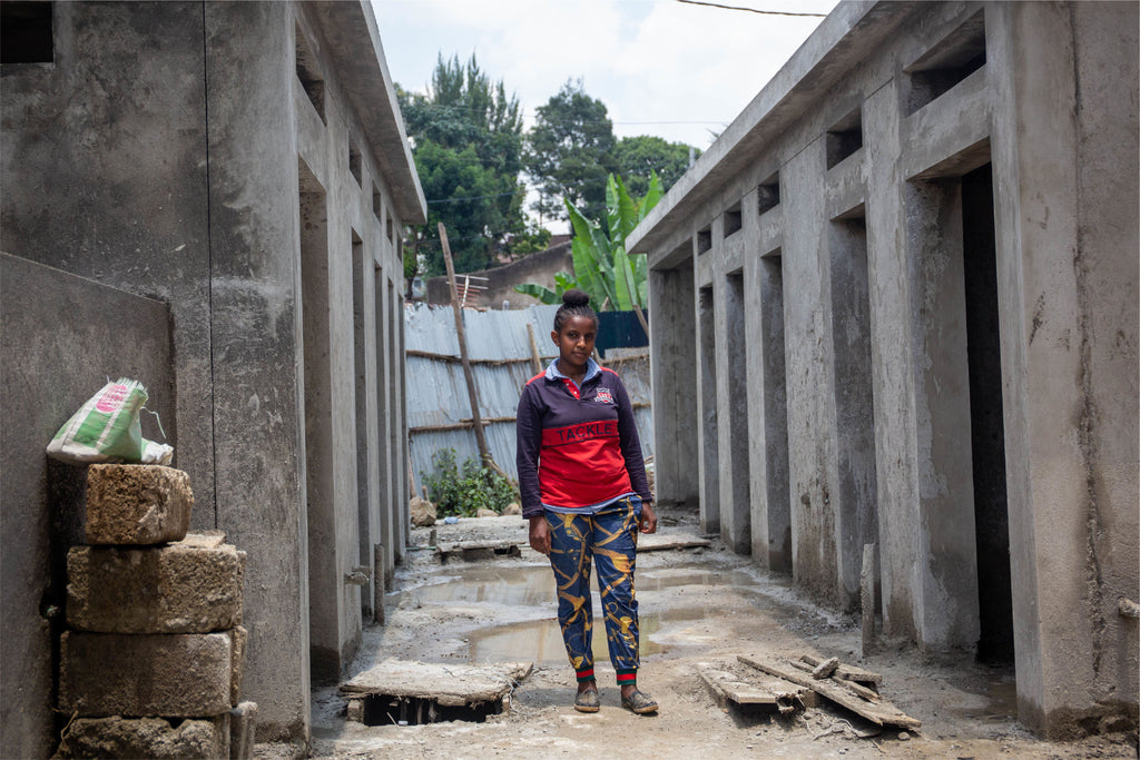 16 year-old Ma'ereg standing in front of the new toilet block