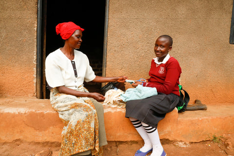 Winfred showing her mother the sanitary pads she made at school