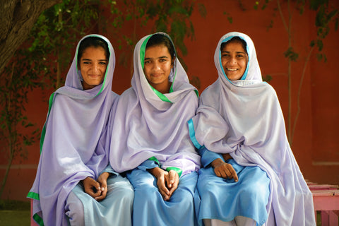 Three school girls from a school in Pakistan, which runs workshops to end period shame.