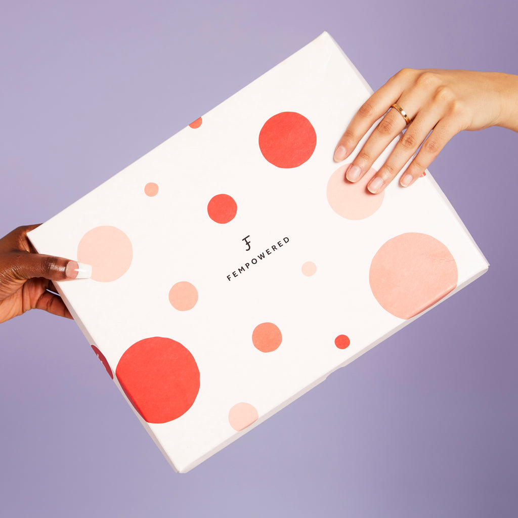 Two hands holding a Fempowered gift box