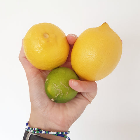 hand holding 2 lemons and 1 lime