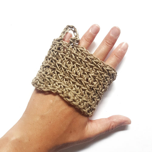 white background, single hand in image with a crocheted band around fingers, designed to exfoliate