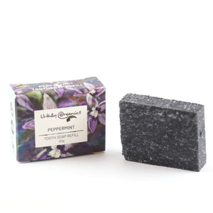 small card board box labelled peppermint toothsoap refill. charcoal block of toothsoap beside box