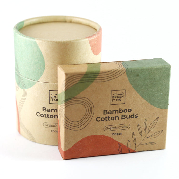 Card board cylindrical tube in back ground. Rectangular cardboard box in foreground. Both labeled with 'bamboo cotton buds'