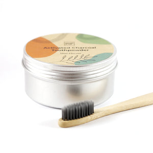 White background, silver tin with activated charcoal toothpowder written on it. bamboo toothbrush with black bristles in the foreground