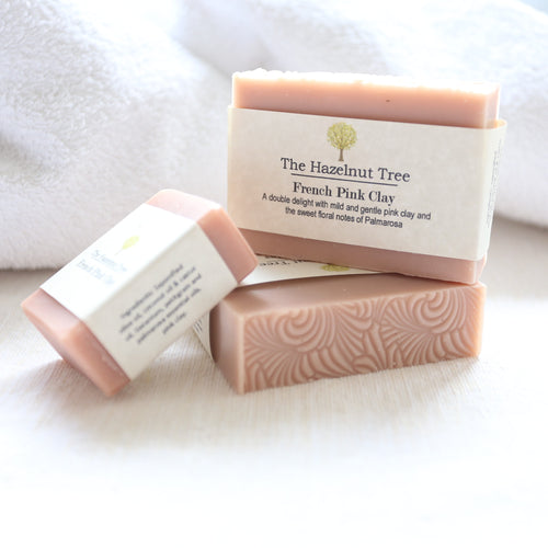 3 pink soaps lying on white towel