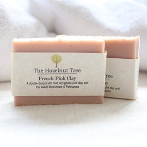 2 pale pink soaps in front of white towel