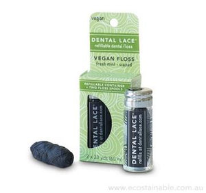 Charcoal dental floss within a glass vial with a black label. Box and spool of charcoal dental floss beside it