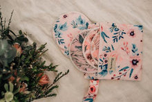 Load image into Gallery viewer, floral printed wet bag with breast pads spilling out of bag