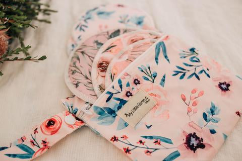 floral printed wet bag with breast pads spilling out of bag