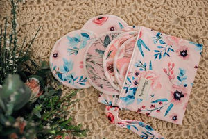 a selection of floral printed breast pads spilling from a small dry bag