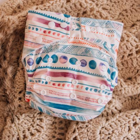 a single nappy with funky colourful print. a combination of lines, zigzags and dots