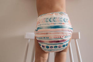 a nappy on a child with funky colourful print. a combination of lines, zigzags and dots