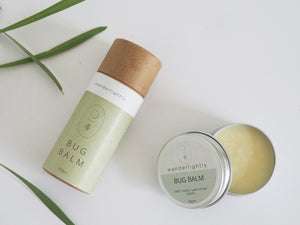birds eye view, white background. Cardboard tube lying down with green label with 'bug balm' on the label. Next to tube is an opened tin with a yellow balm inside. Lid of tin is labeled 'bug balm'. Some green foliage in the background