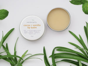 white background, foliage in background. 1 tin which is opened, containing cocoa and vanilla lip balm