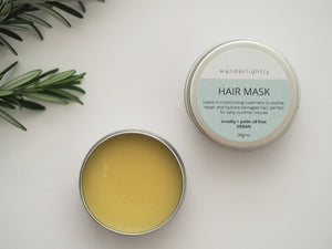 white background, rosemary sprig in corner of image. Tin of balm in image with lid beside the tin labeled 'Hair mask'