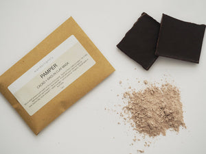Small card envelope labelled 'pamper. cacao and kaolin clay mask'. some dry clay powder and dark chocolate in the image