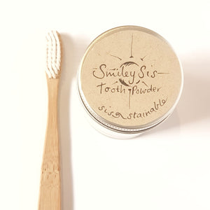 Bamboo toothbrush and jar of white powder labeled 'smiley sis tooth powder'