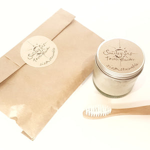 Birds eye view of paper bag sealed with label that reads 'tooth powder'. Glass jar with label that reads 'smiley sis toothpowder'. bamboo toothbrush.