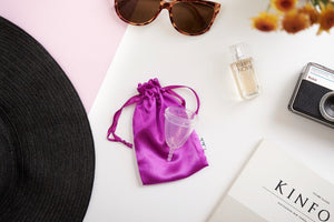 a menstrual cup on top of fabric pouch
