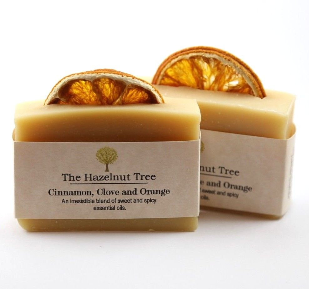 2x pale yellow soaps with a dried orange slice embedded in the top