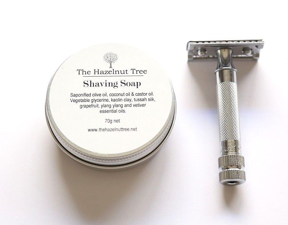 small silver tin containing shaving soap. Silver safety razor beside tin