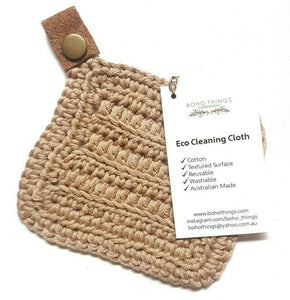 A single square crocheted cloth, made from beige cotton with a small leather loop attached to a corner