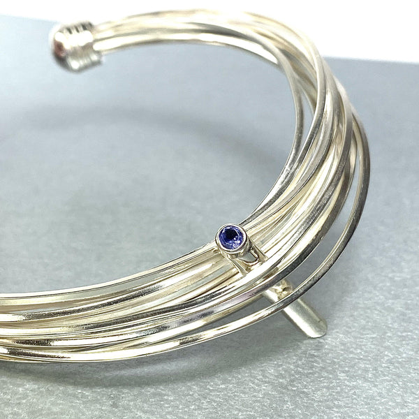 Solitaire: silver torque bangle with an Iolite