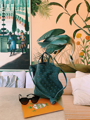 teal block printed suede llani handbag in front of a hand painted wall in jaipur india