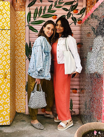 two women wearing bright colors in from of a wallpapered wall