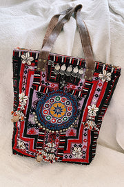 cowrie embellished tote bag in vibrant red and purple, on white background.