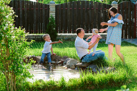 Happy family playing in a garden with pond