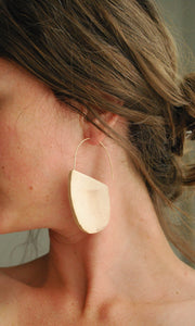 profile of a brown-haired woman wearing driftwood and gold hoops