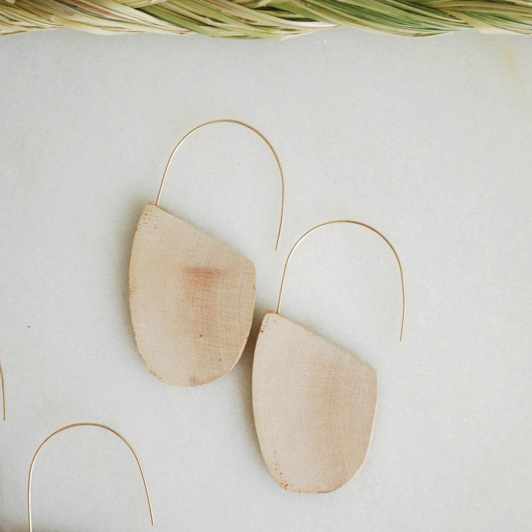 a pair of earrings with light colored driftwood cut into half-oval shapes hang on gold wire