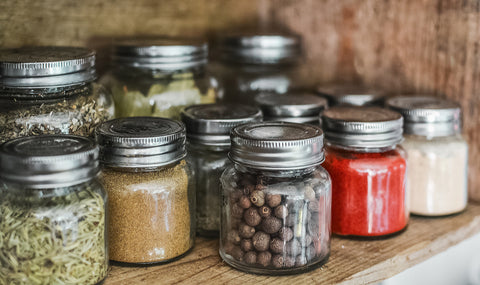 small spice jars in a wooden cabinet